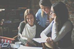 Jonge studentenmeisjes die thuis boek lezen stock foto