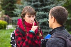 Jonge studentenvrienden die bij universiteit spreken stock afbeelding