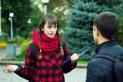Jonge studentenvrienden die bij universiteit spreken royalty-vrije stock foto
