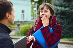 Jonge studentenvrienden die bij universiteit spreken Het meisje probeert om te tonen hoe haar echtgenoot in liefde verklaarde stock foto's
