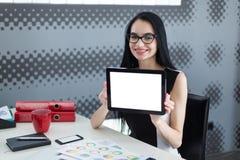 Jonge studentenvrouw die in bureau een tablet en het glimlachen houden Stock Foto's