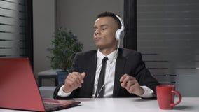 Jonge succesvolle Afrikaanse zakenman die in kostuum aan muziek op de computer in hoofdtelefoons luisteren, die in het bureau dan stock footage