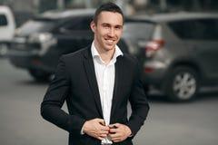 Jonge succesvolle glimlachende mens in een zwart kostuum, op de straat, op de achtergrond van auto's Gelukkige moderne mens outdo Stock Foto