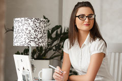 Jonge succesvolle glimlachende vrouw die glazen dragen die thuis in haar eigen kabinet werken Stock Afbeeldingen