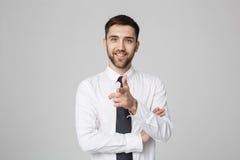 Jonge succesvolle zakenman die richting met vinger over donkere grijze achtergrond richten De ruimte van het exemplaar royalty-vrije stock afbeeldingen
