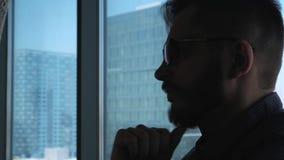 Jonge succesvolle zakenman met een baard die op de achtergrond van een venster denken die van de binnenstad overzien Hoge zaken stock video