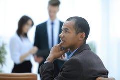 Jonge succesvolle zakenman op achtergrond van bureau royalty-vrije stock afbeelding