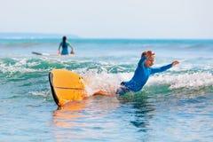 Jonge surfer het leren rit en daling van surfplank met pret stock afbeelding