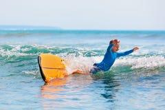 Jonge surfer het leren rit en daling van surfplank met pret stock fotografie