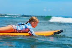 Jonge surferpeddel op surfplank met pret op overzeese golven stock afbeeldingen