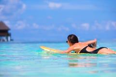 Jonge surfervrouw die tijdens strandvakantie surfen Royalty-vrije Stock Foto