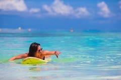 Jonge surfervrouw die tijdens strandvakantie surfen Stock Afbeeldingen