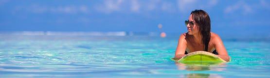 Jonge surfervrouw die tijdens strandvakantie surfen Stock Foto's