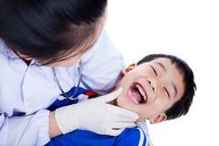 Jonge tandarts die mondelinge gezondheid van kind controleert, op wit Royalty-vrije Stock Afbeelding