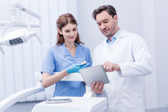 Jonge tandartsen die het werk bespreken samen en tablet in tandkliniek gebruiken royalty-vrije stock fotografie