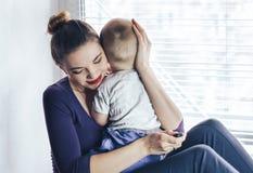 Jonge tedere gelukkige moeder die haar pasgeboren baby het glimlachen zitting op vensterbank in ochtend koesteren Het genieten va Stock Foto