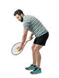 Jonge tennisspeler die in polooverhemd bal voorbereidingen treffen te dienen Stock Foto