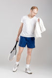 Jonge tennisspeler met het tennisracket van de handdoekholding na opleiding op grijze achtergrond Royalty-vrije Stock Foto's