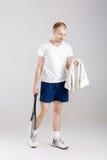 Jonge tennisspeler met het tennisracket van de handdoekholding na opleiding op grijze achtergrond Royalty-vrije Stock Foto
