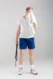 Jonge tennisspeler met het tennisracket van de handdoekholding na opleiding op grijze achtergrond Royalty-vrije Stock Afbeelding