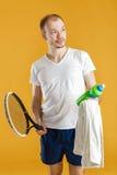 Jonge tennisspeler met het tennisracket van de handdoekholding op gele achtergrond Stock Afbeeldingen