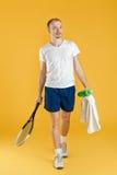Jonge tennisspeler met het tennisracket van de handdoekholding op gele achtergrond Royalty-vrije Stock Foto's