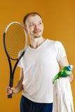 Jonge tennisspeler met het tennisracket van de handdoekholding op gele achtergrond Stock Afbeelding