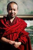 jonge tibetan boeddhistische monnik in een rode kleding voor zijn kloostertempel royalty-vrije stock afbeelding