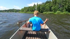 Jonge tiener die een roeiboot of een peddelboot op een meer met bos roeien bij bank Blauwe de zomerhemel stock videobeelden