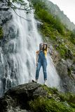 Jonge tiener die zich op de grote steen dichtbij waterval bevinden stock foto's