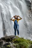 Jonge tiener die zich op de grote steen dichtbij waterval bevinden royalty-vrije stock foto's
