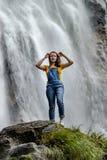 Jonge tiener die zich op de grote steen dichtbij waterval bevinden royalty-vrije stock afbeeldingen