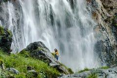 Jonge tiener die zich op de grote steen dichtbij waterval bevinden stock afbeelding