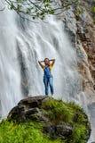 Jonge tiener die zich op de grote steen dichtbij waterval bevinden stock afbeeldingen