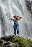 Jonge tiener die zich op de grote steen dichtbij waterval bevinden stock foto
