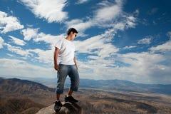 Jonge tiener die zich op een rots bevinden Stock Foto's