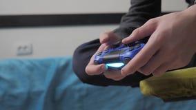 Jonge tiener en van de bedieningshendelmens sweater met een kap die in online videospelletje wordt geabsorbeerd jongenstiener in  stock video