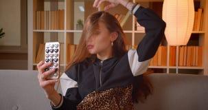 Jonge tienerblogger maakt verleidelijke selfie-foto's thuis op cellphonezitting op bank op boekenrekkenachtergrond stock videobeelden