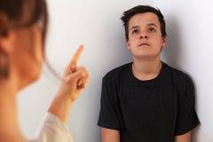 Jonge tienerjongen bored door het constante spreken en de confrontatie met zijn moeder stock foto's