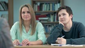 Jonge tienerleerlingen in klasse, die aan een leraar luisteren stock videobeelden