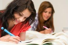 Jonge tienermeisjes die op bed bestuderen Stock Foto
