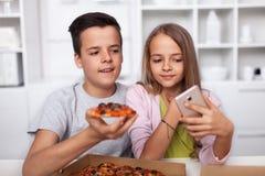 Jonge tieners die een selfie met hun pizza in de keuken nemen royalty-vrije stock afbeeldingen
