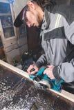 Jonge timmerman met een baard die met een elektrisch vliegtuig zonder zuiging die van zaagsel werken en houten bars nivelleren sc stock afbeelding