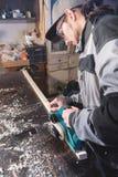 Jonge timmerman met een baard die met een elektrisch vliegtuig zonder zuiging die van zaagsel werken en houten bars nivelleren sc stock foto