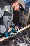 Jonge timmerman met een baard die met een elektrisch vliegtuig zonder zuiging die van zaagsel werken en houten bars nivelleren sc stock foto's
