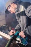 Jonge timmerman met een baard die met een elektrisch vliegtuig met zuiging die van zaagsel werken en houten bars nivelleren schur stock afbeelding
