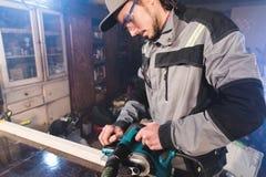 Jonge timmerman met een baard die met een elektrisch vliegtuig met zuiging die van zaagsel werken en houten bars nivelleren schur stock foto's
