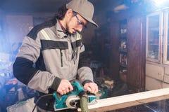 Jonge timmerman met een baard die met een elektrisch vliegtuig met zuiging die van zaagsel werken en houten bars nivelleren schur stock foto
