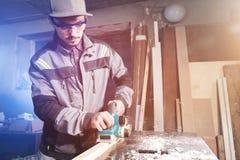 Jonge timmerman met een baard die met een elektrisch vliegtuig met zuiging die van zaagsel werken en houten bars nivelleren schur stock fotografie