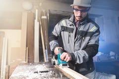 Jonge timmerman met een baard die met een elektrisch vliegtuig met zuiging die van zaagsel werken en houten bars nivelleren schur stock afbeeldingen